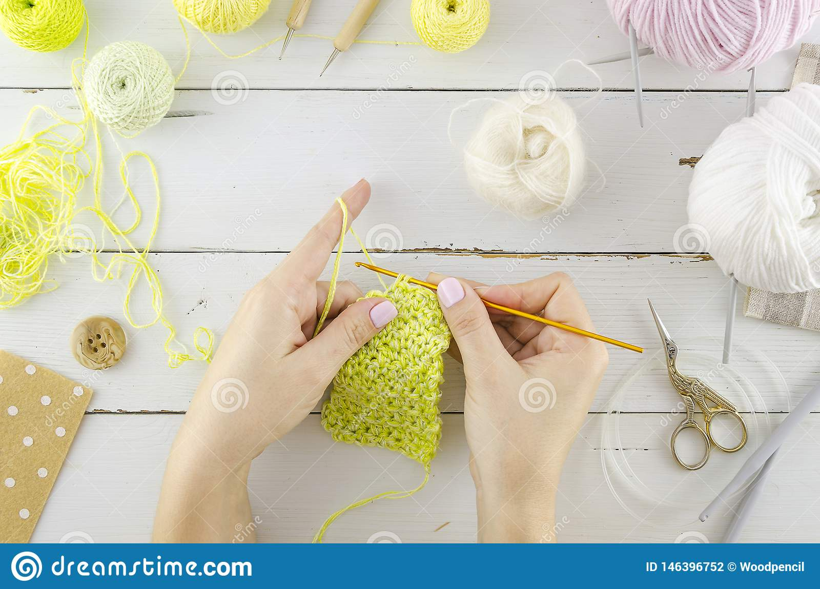 Woman knits clothes. Top view white desk with tools and knitting accessories. Women`s hands hold knitting needles