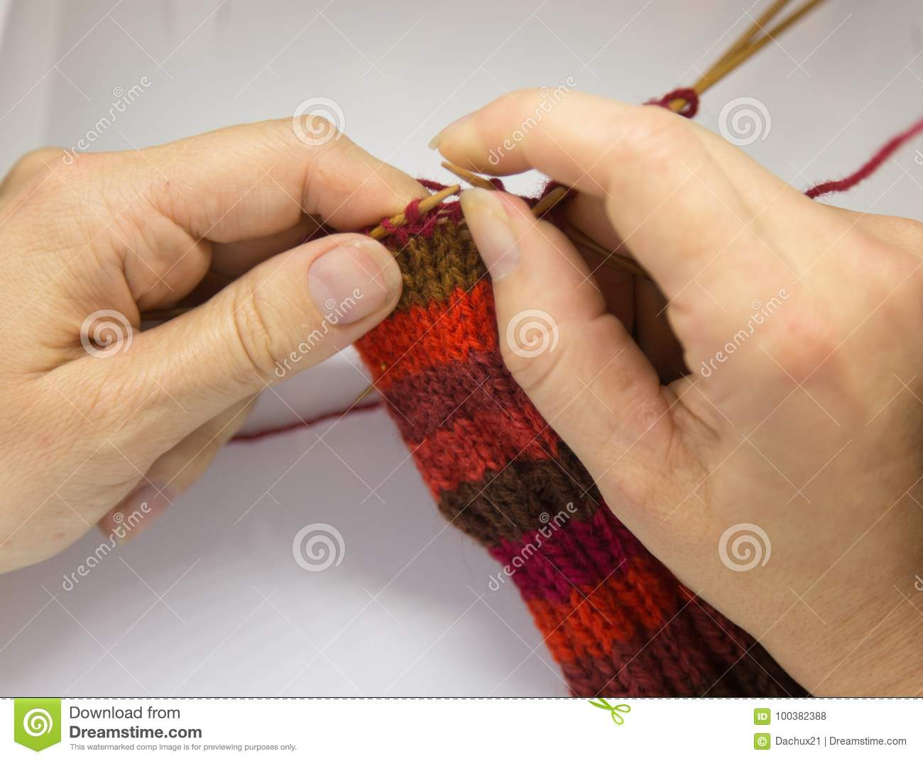 A woman knitting red woolen socks. Knitting close up on a white background. Hand crafts.