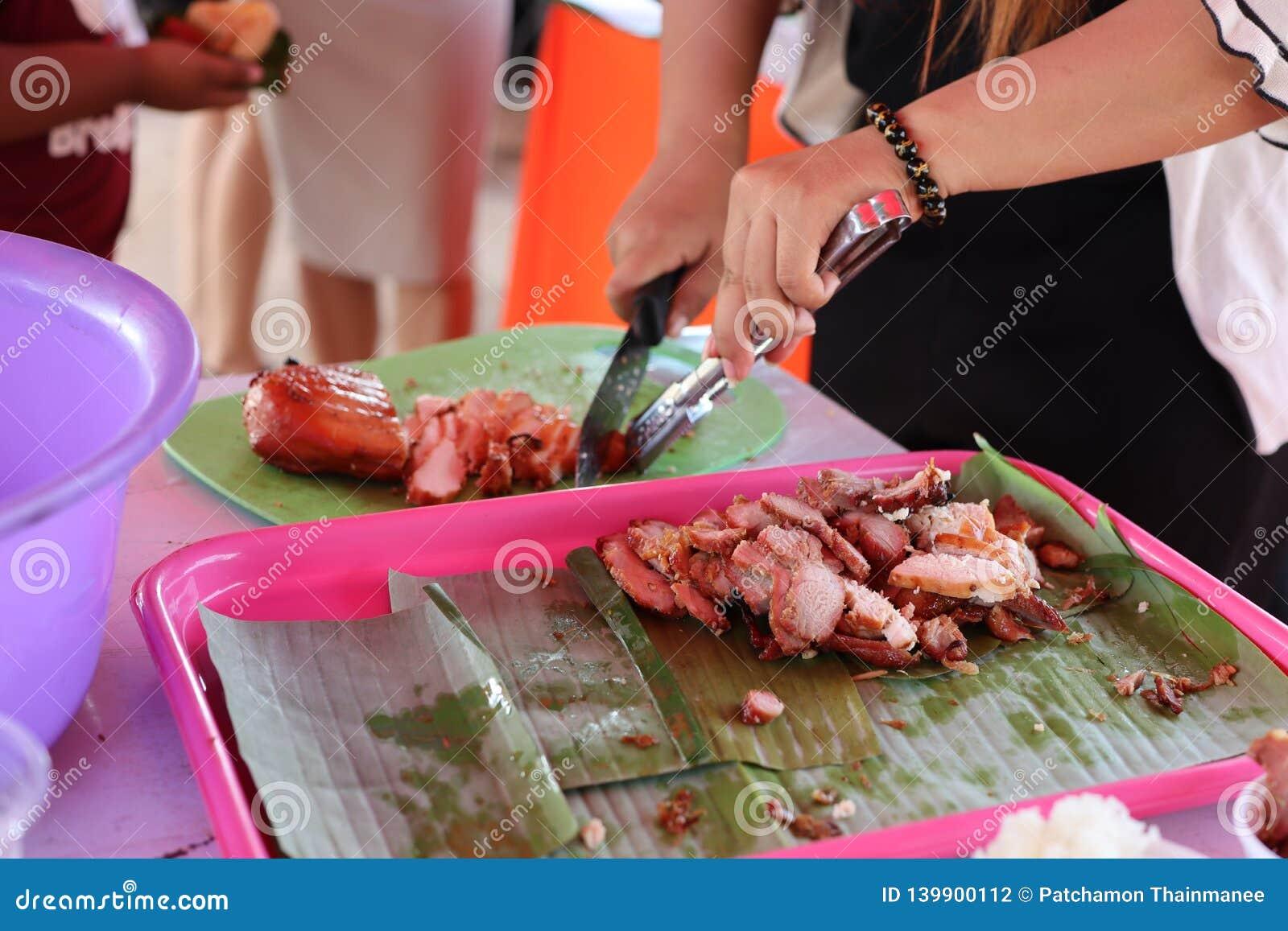 Woman& x27; la mano di s sta utilizzando un coltello tagliente Carne di maiale affettata del ‹del †del ‹del †sul tagliere