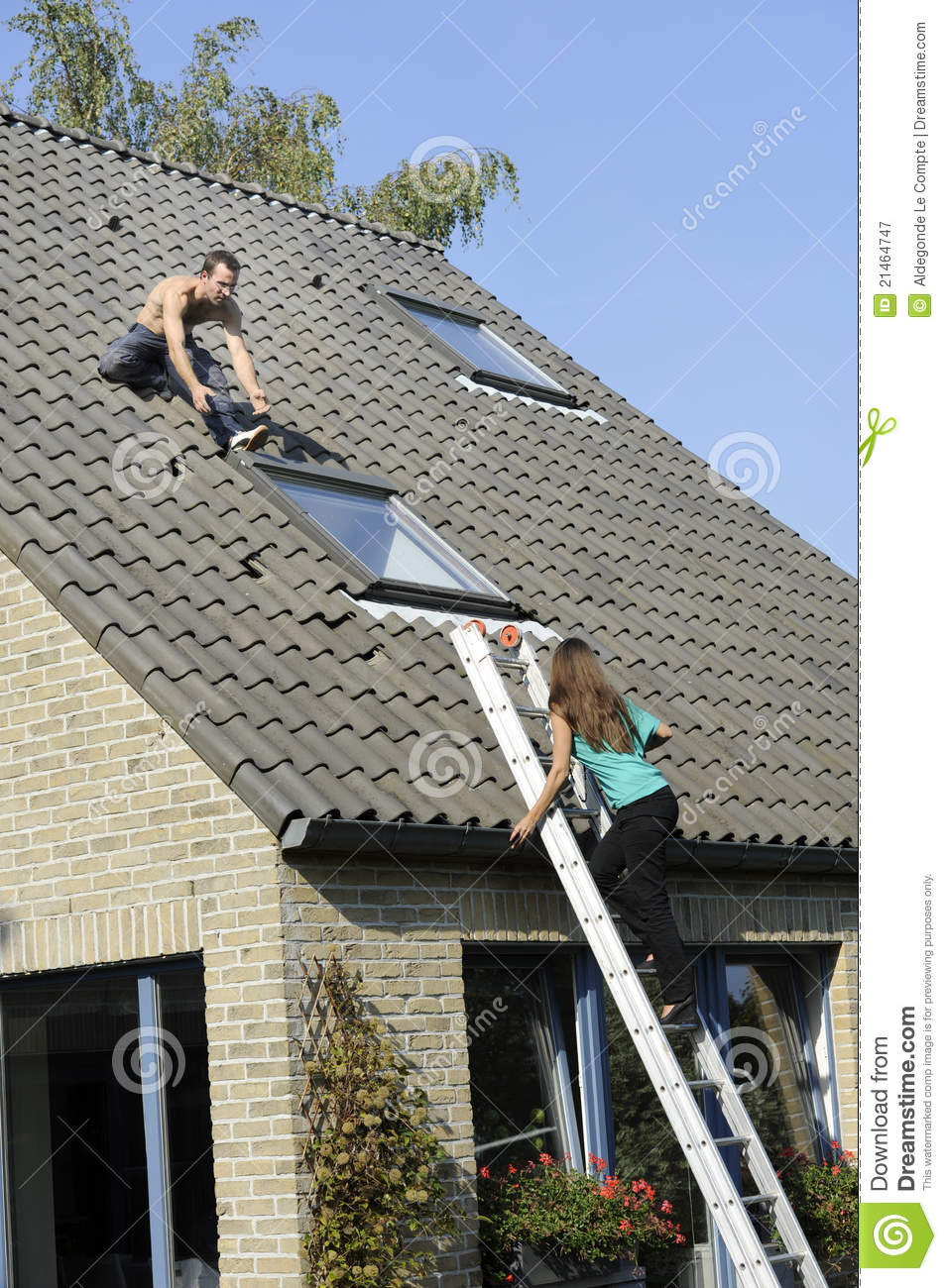 Woman On Ladder And Roofer Working On A Roof Royalty Free