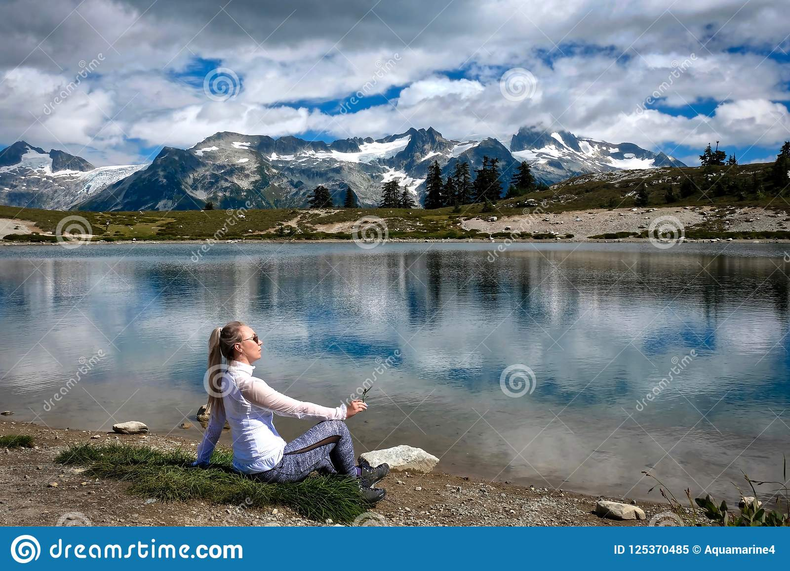 Woman on the lake shore meditating and relaxing. Beautiful view of mountains and reflections in the lake.