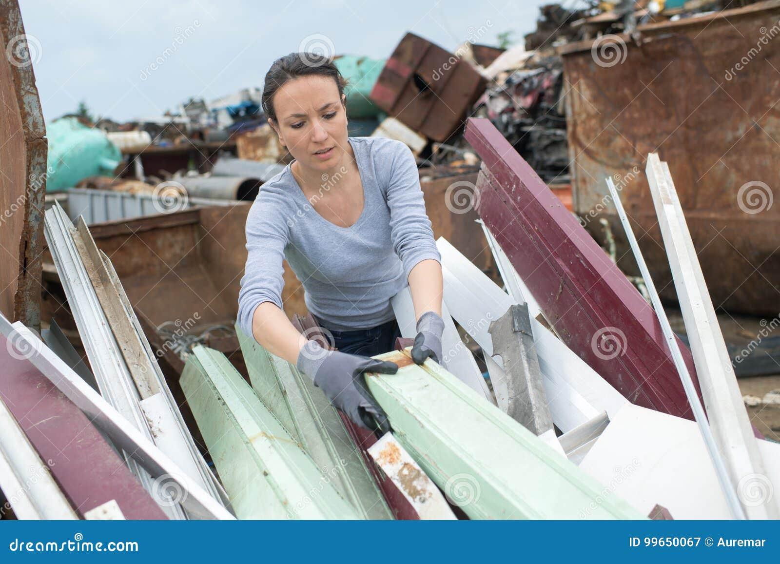 Woman landfill employee working in skip