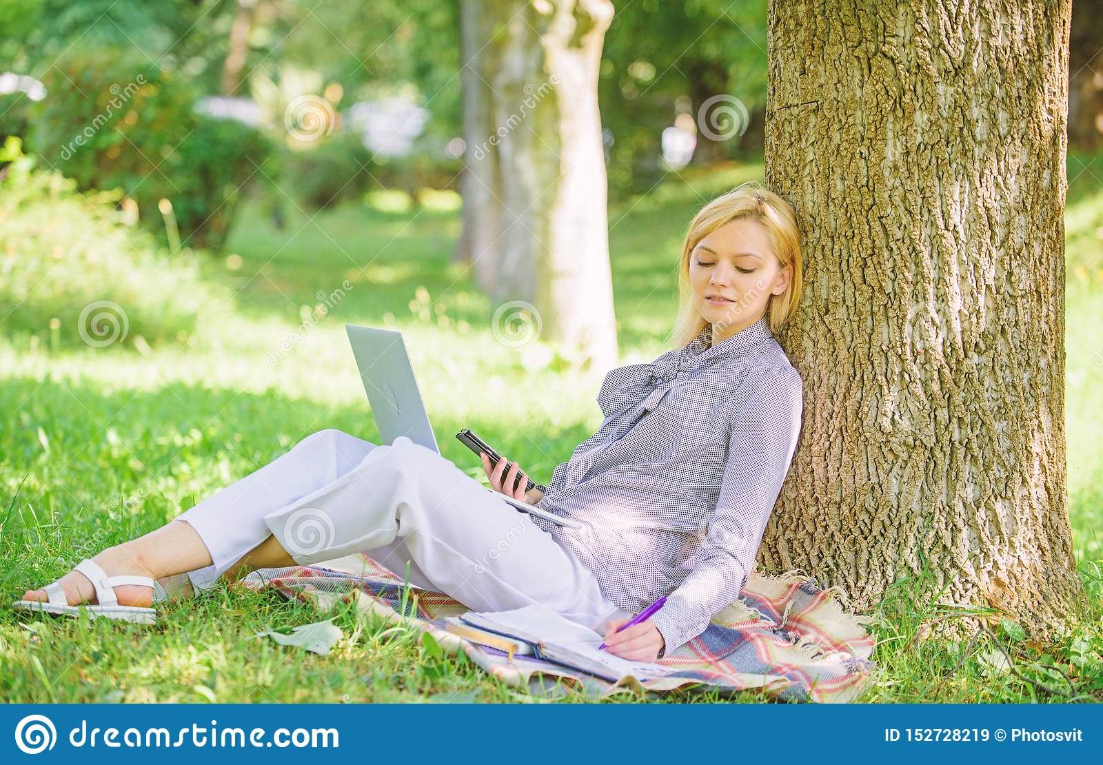 Woman with laptop computer work outdoors lean on tree trunk. Girl work with laptop in park sit on grass. Natural