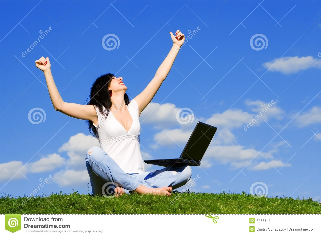 Woman with laptop on the green grass