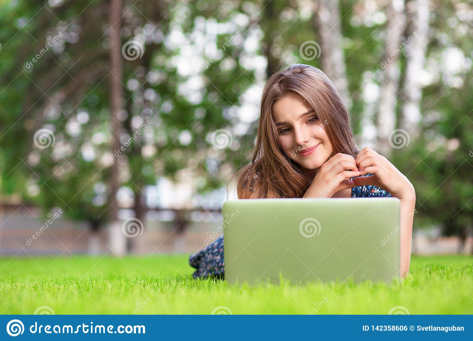 Woman with laptop at home happy showing love with hands in heart shape