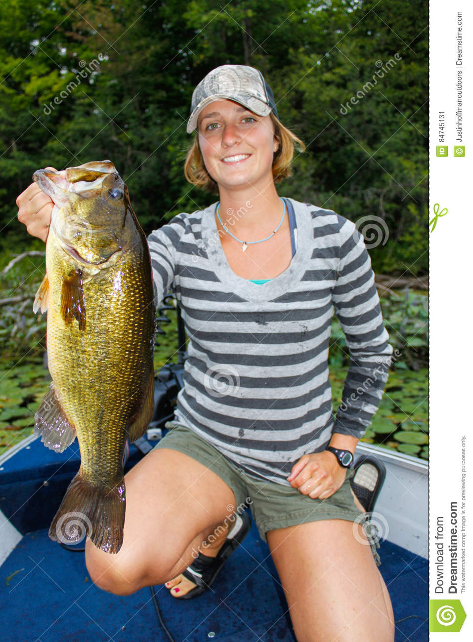 Woman largemouth bass fishing stock image image 84745131 for Best time for bass fishing