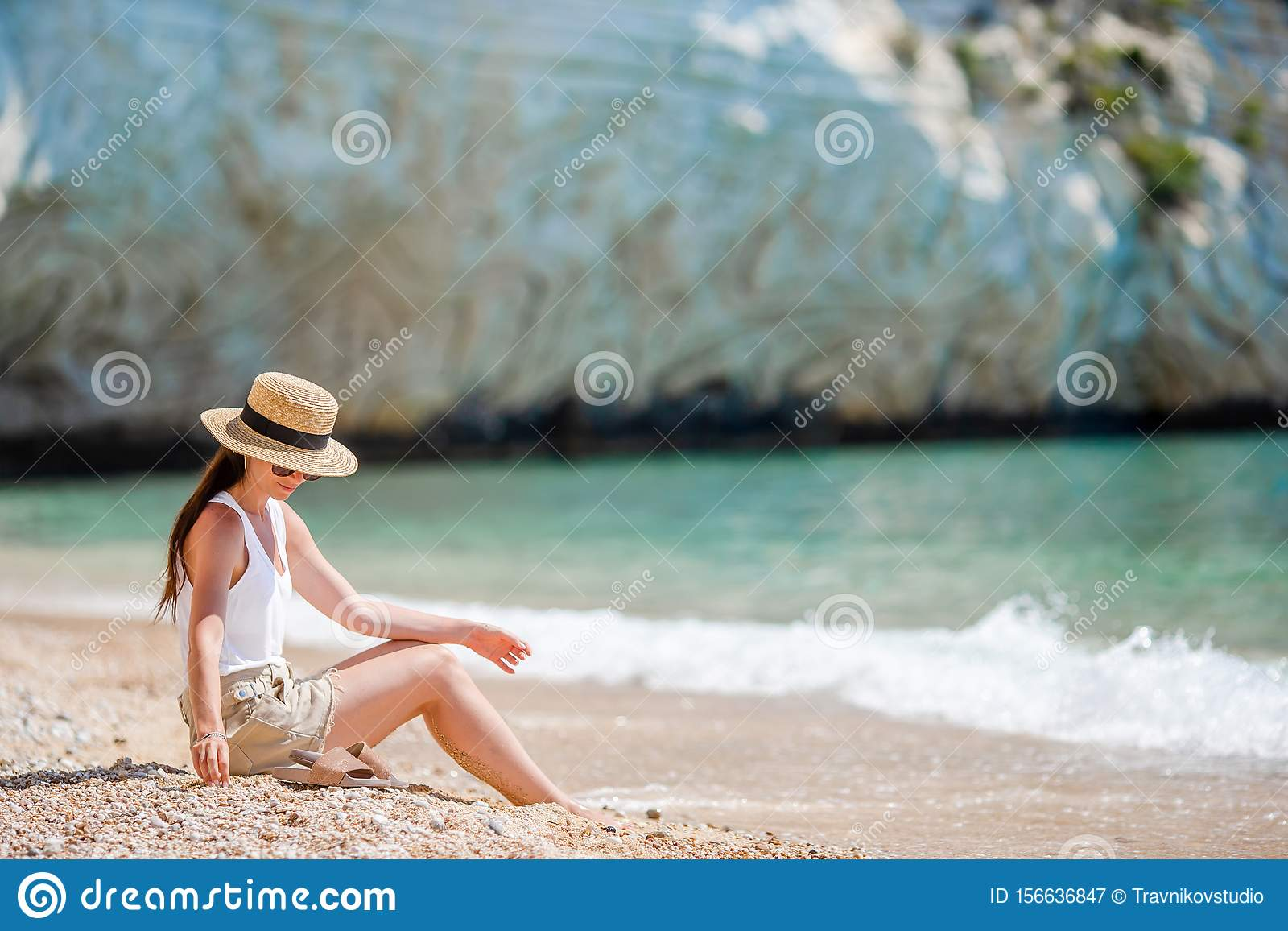 Woman laying on the beach enjoying summer holidays looking at the sea