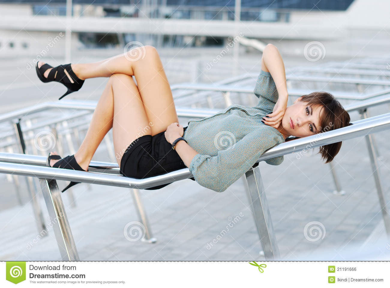 Woman lays on a metal handrail