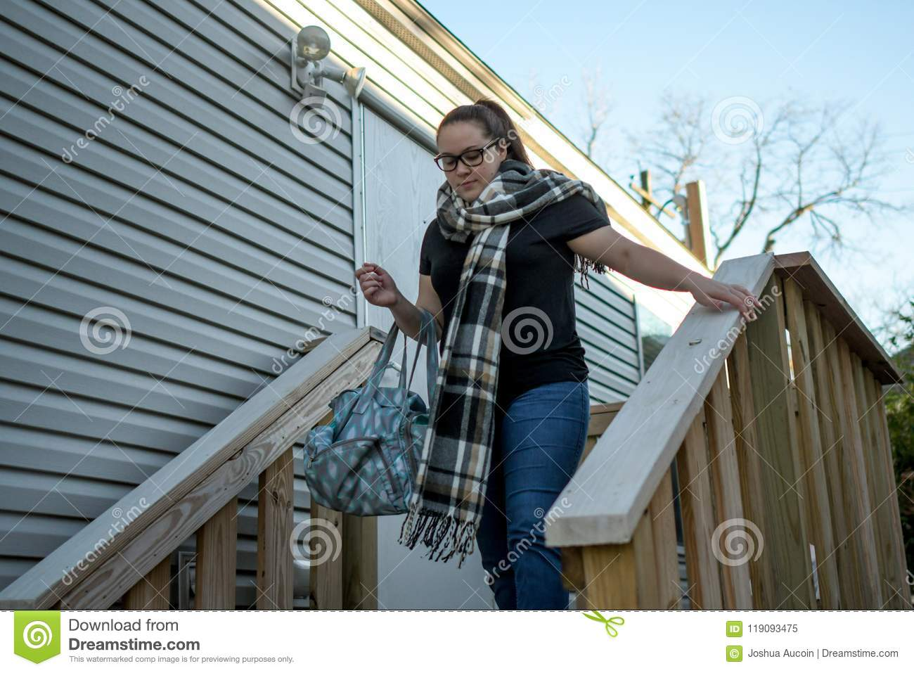 Woman leaves home with bag draped over her arm.