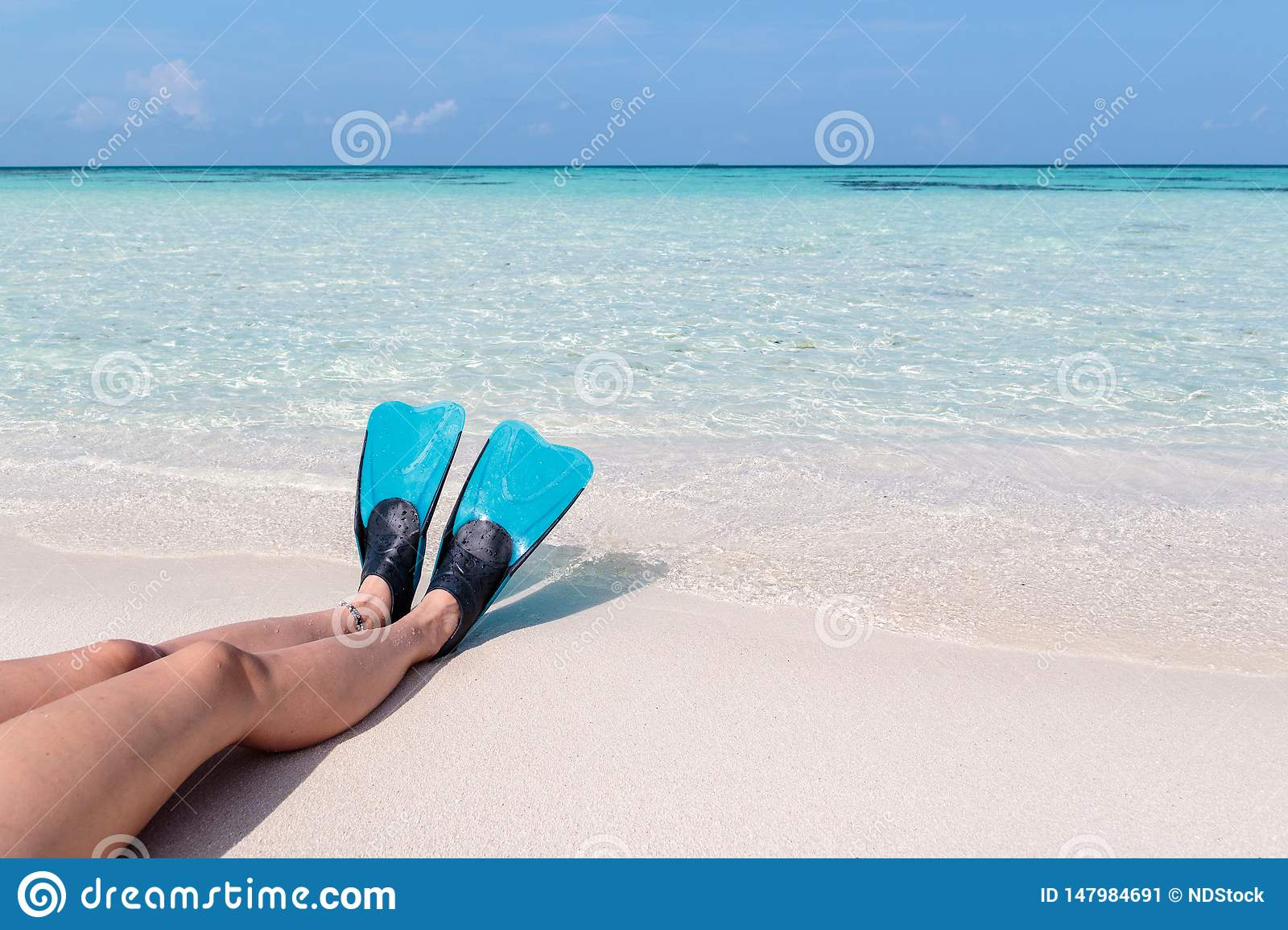 Woman legs with flippers on a white beach in the Maldives. Crystal clear blue water as background