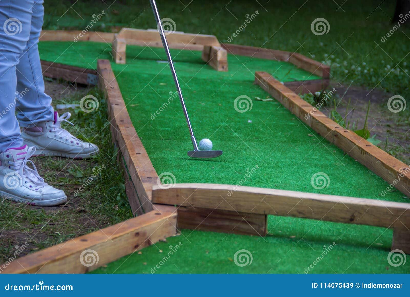 Woman legs, golfing on the green, woman putting ball. Final shot, Golf