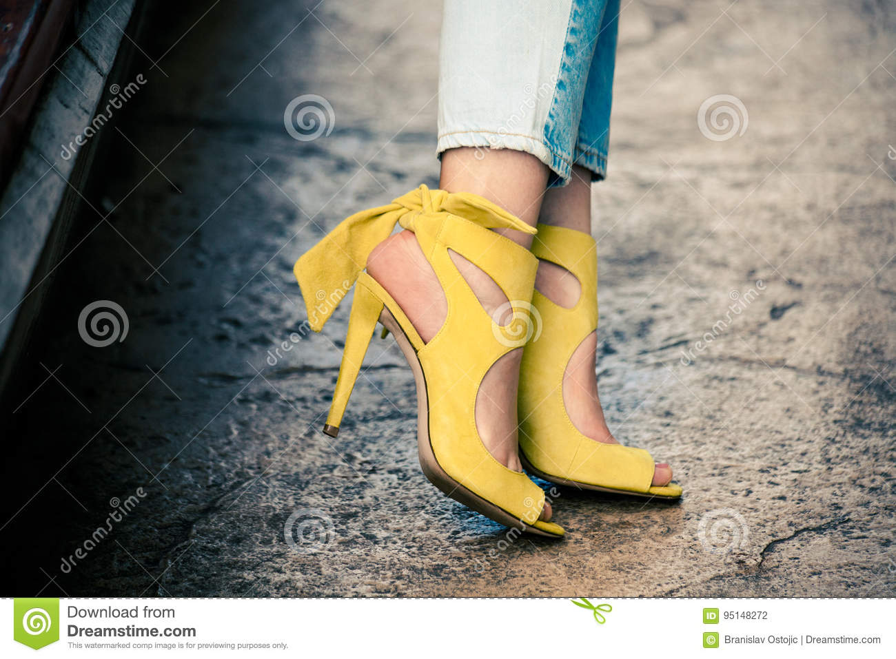 Woman legs in leather yellow high heel sandals outdoor in city