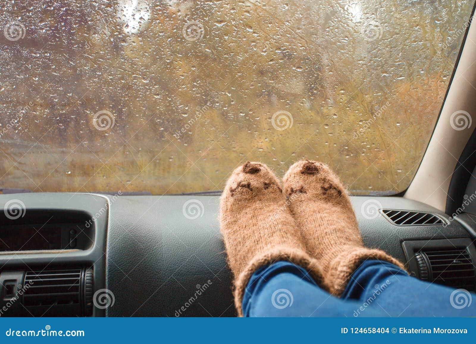 Woman legs in warm cute socks on car dashboard. Drinking warm tee on the way. Fall trip. Rain drops on windshield. Freedom travel