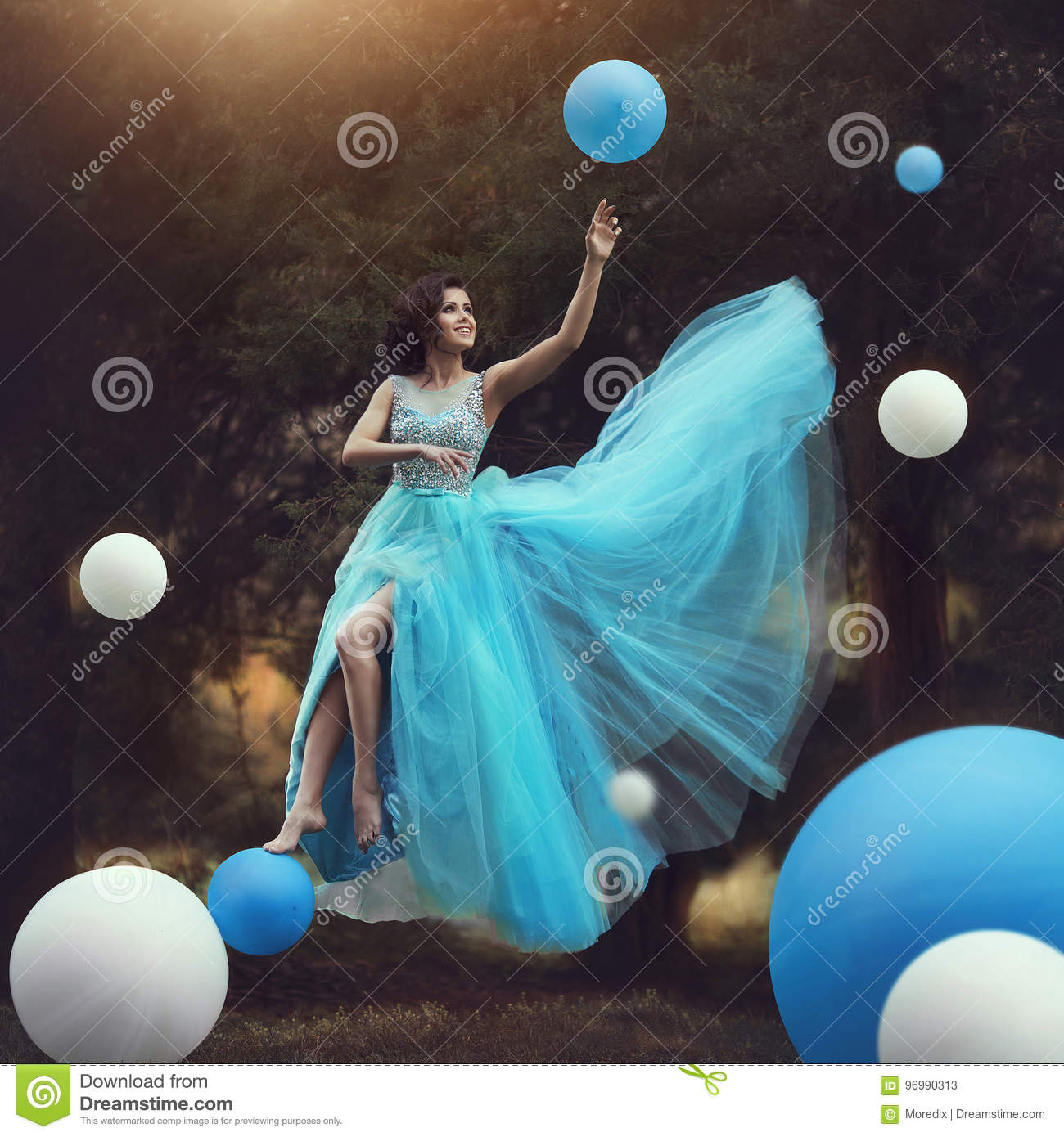 The Woman levitates. A beautiful girl in a blue fluffy gown Leets along with balloons. Dynamic art photography. Fantasy