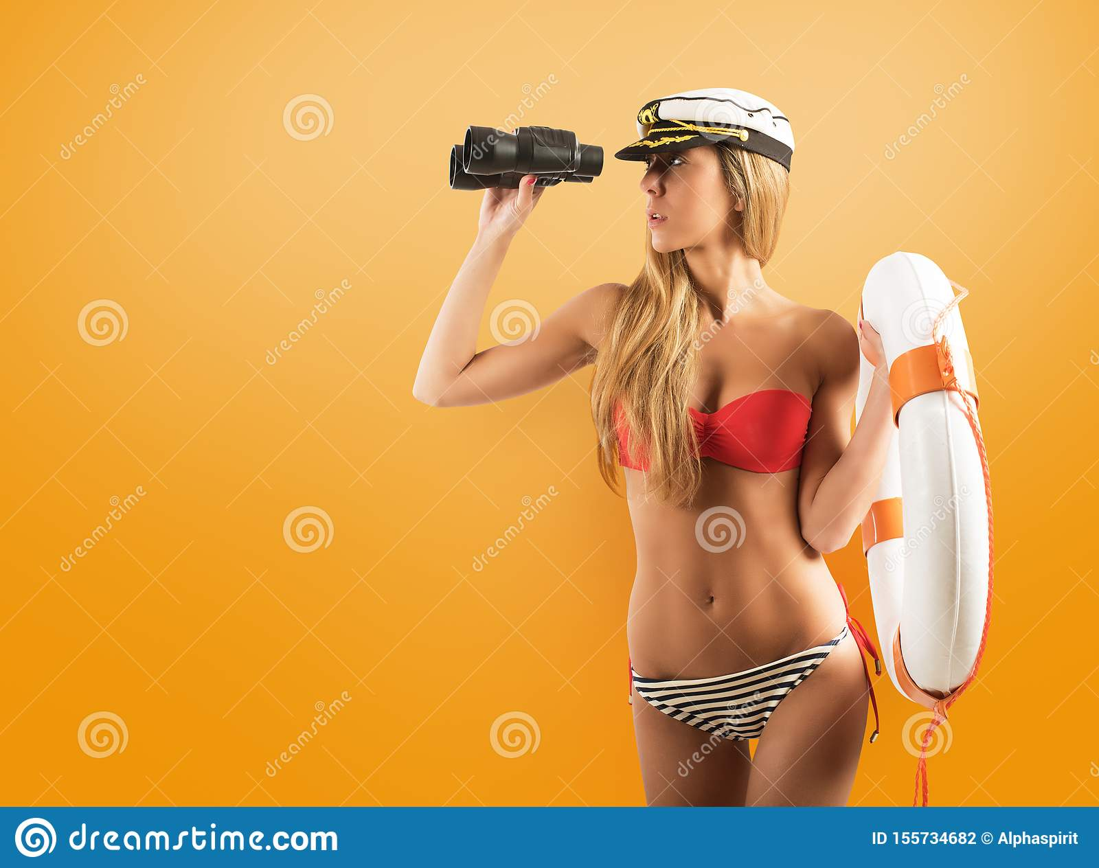 Woman with lifesaver looking out to sea with binoculars