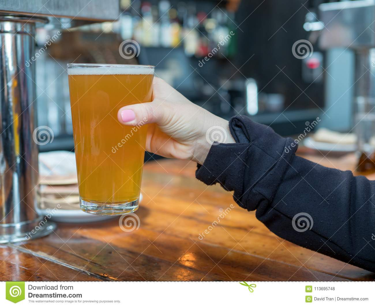 Woman lifting up pint glass of IPA beer in a bar