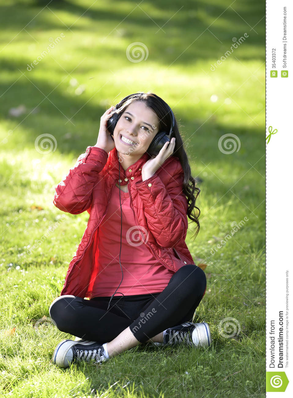 Student girl outside in park listening to music on headphones while