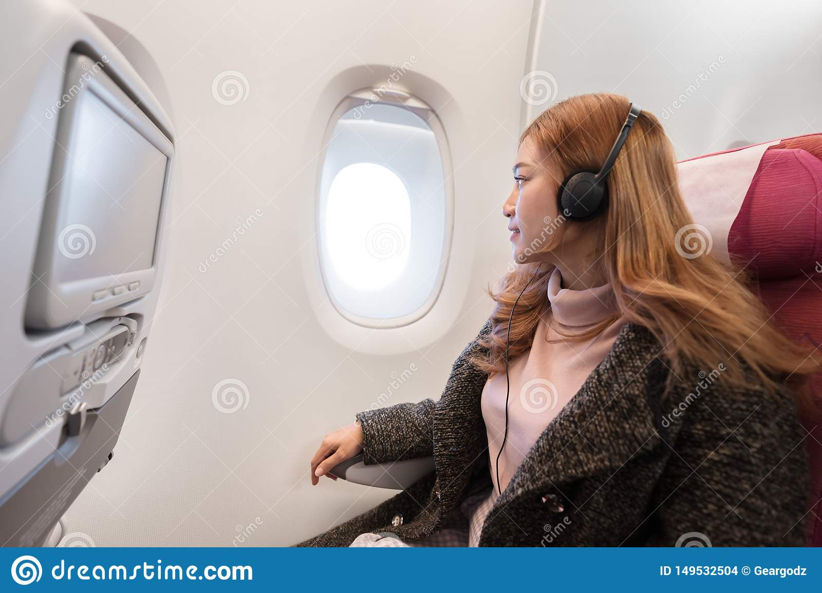 Woman listening to music with headphones on airplane in flight time