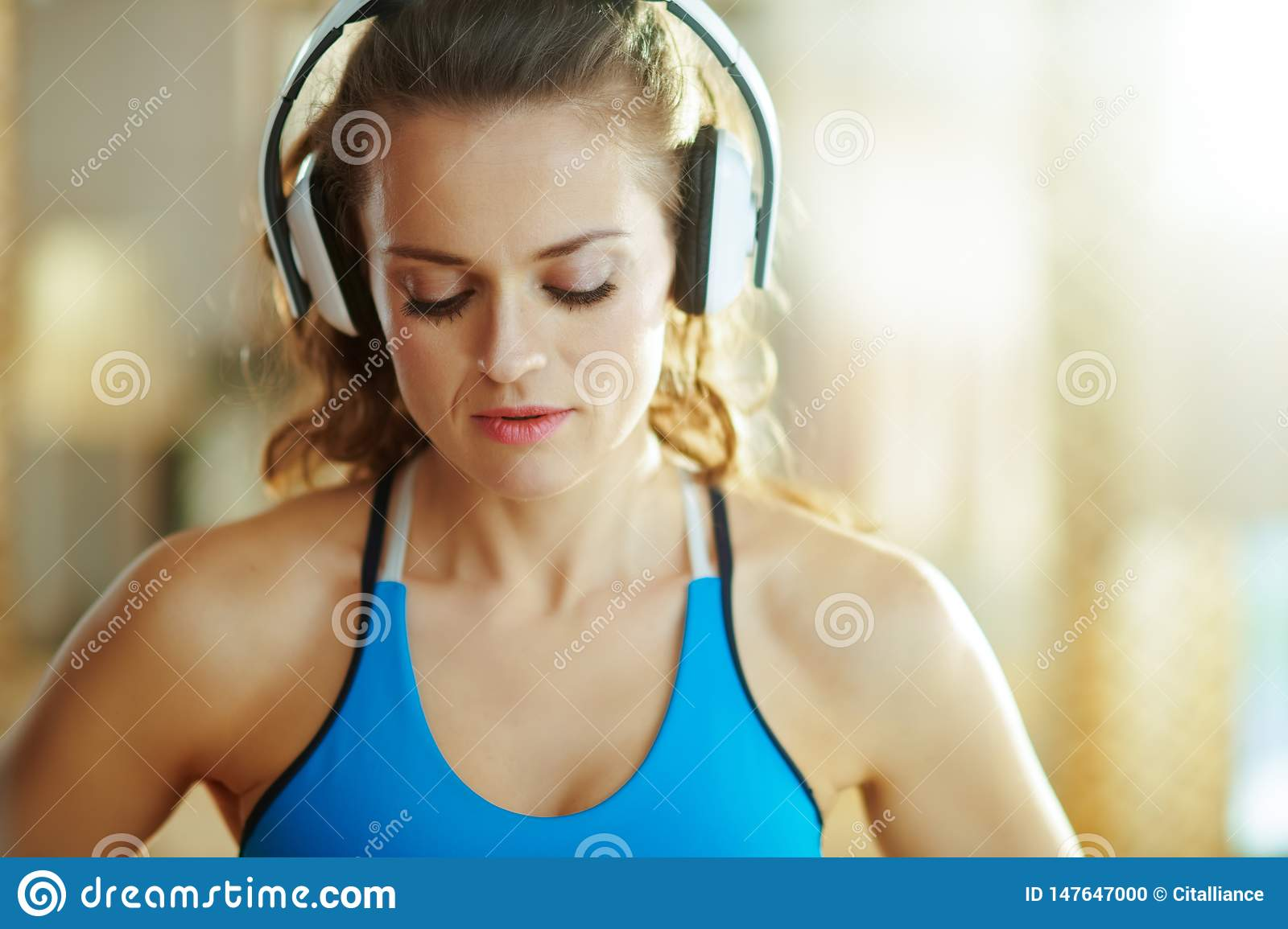 Woman listening to music with headphones in modern house