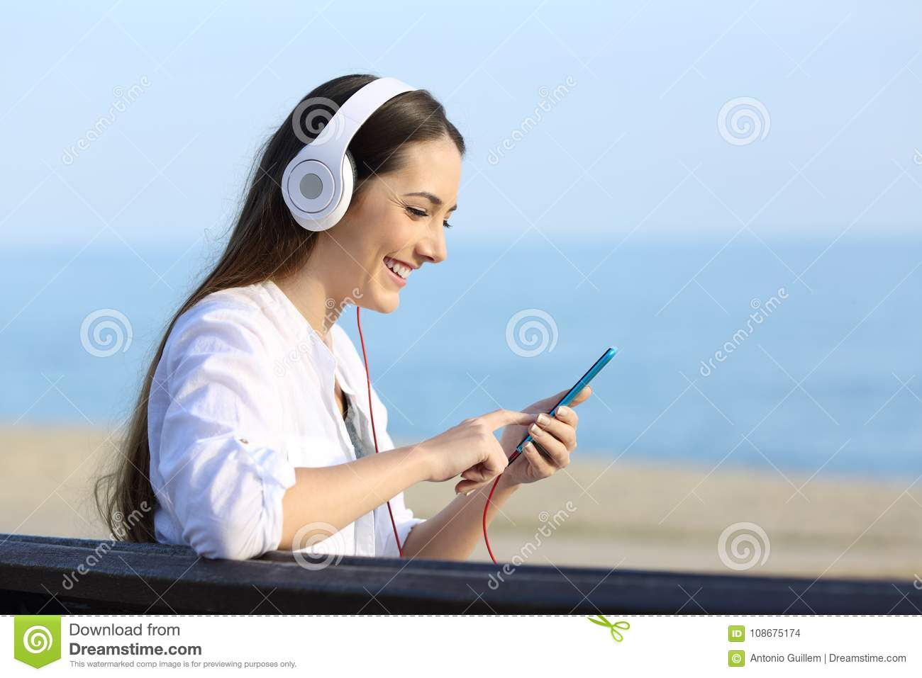 Woman listening to music sitting on a bench on the beach