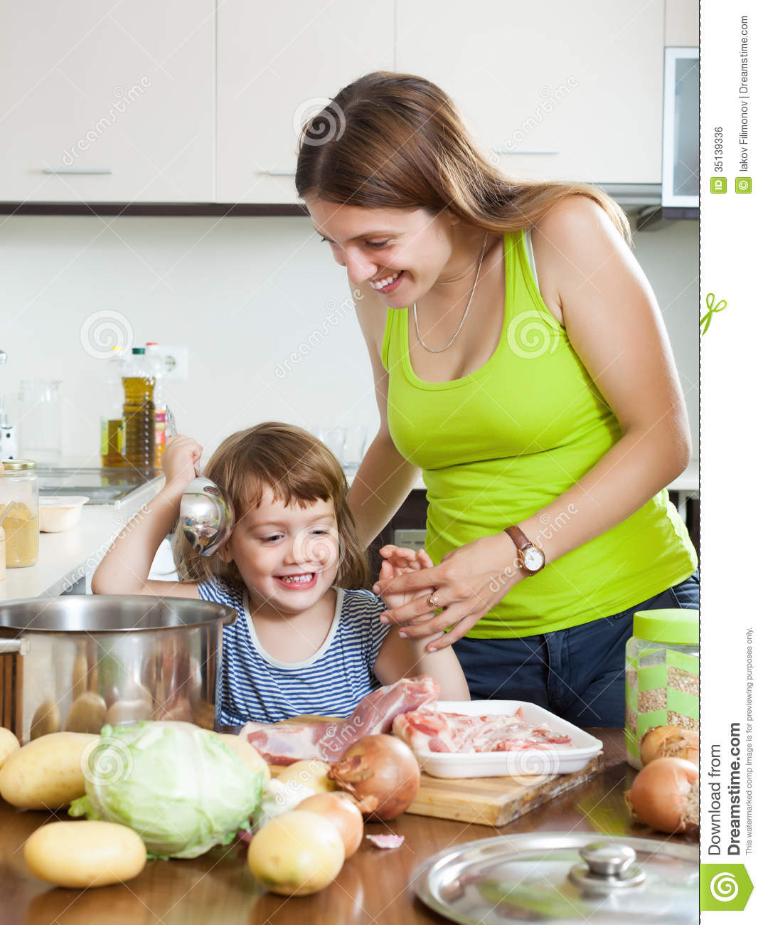 Women Kitchen: Woman With Little Girl Cooking Together Stock Photo