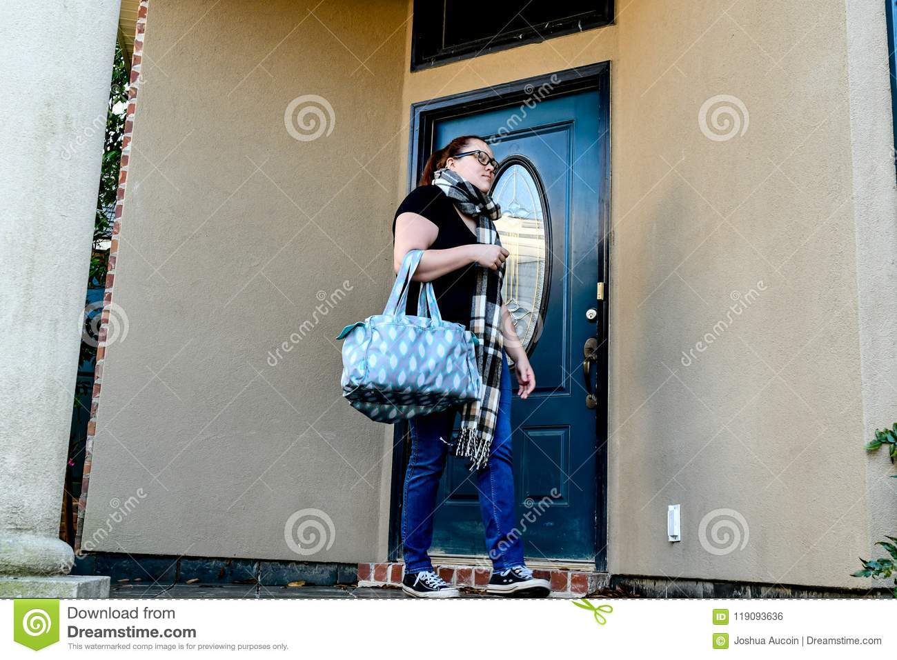A woman locks her front door as she leaves home with a duffel bag over one arm.