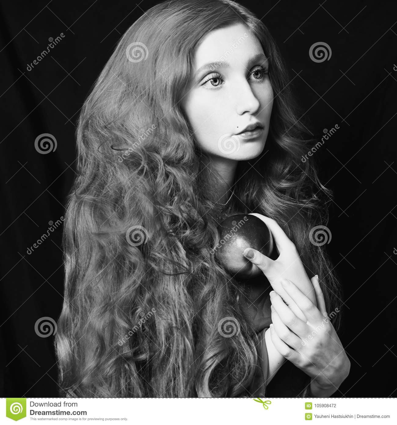 Woman with long curly flowing hair on a black background natural beauty the girl from the era of renaissance black and white art monochrome photography