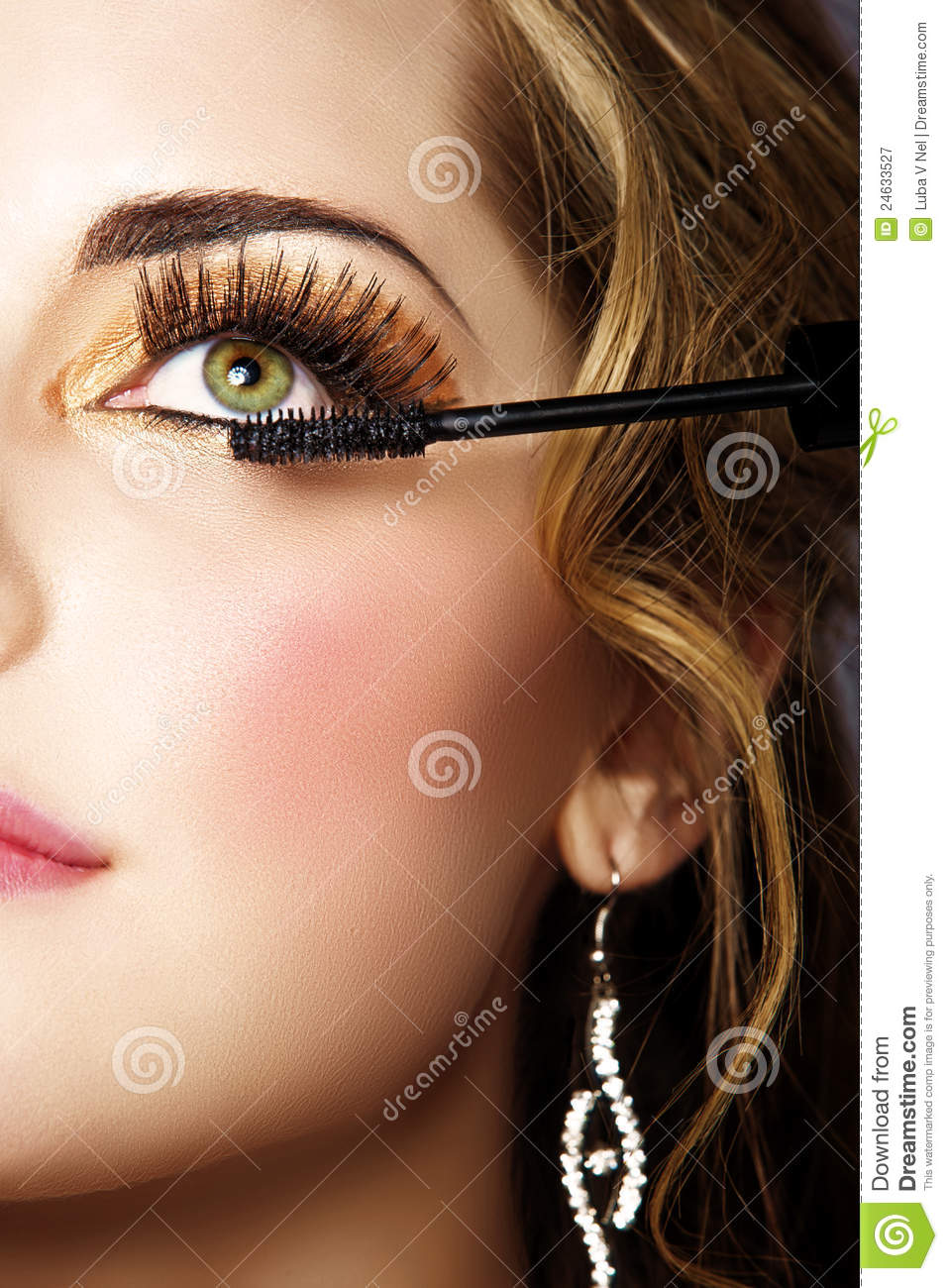86d8ee32bc6 Portrait of beautiful woman with smoky gold eyeshadow and long false  eyelashes applying mascara with a wand