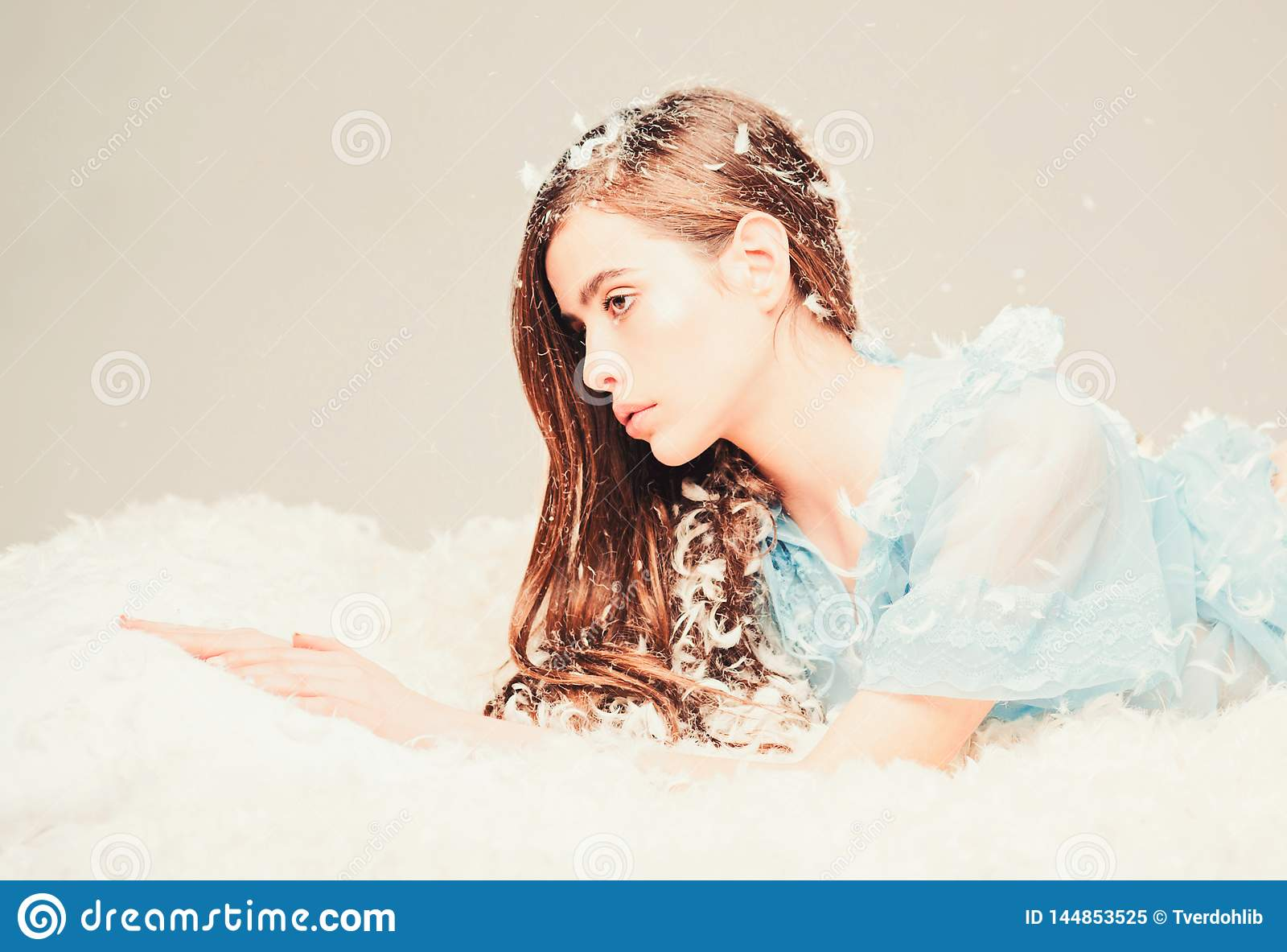 Woman with long hair in tender pajama relaxing. Lady in transparent blue nightie lay on bed, grey background. Girl on