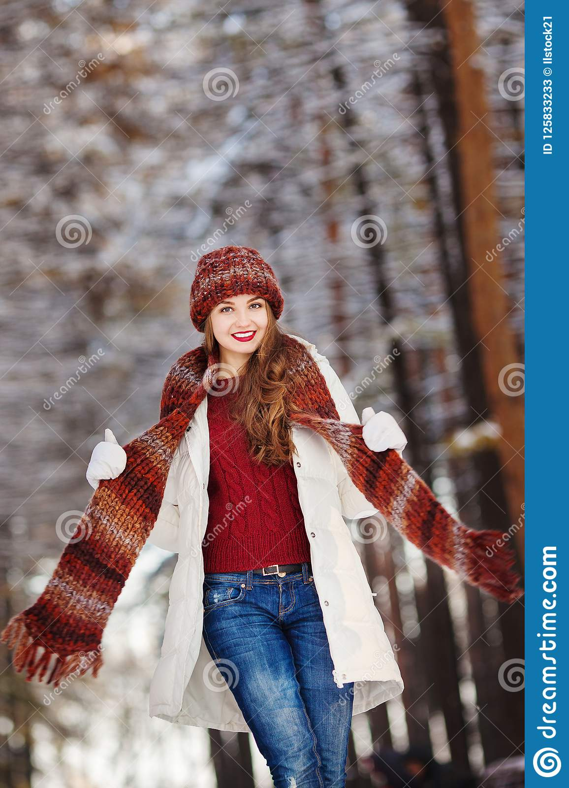 4432cd14bc50c Woman with long hair and knitted scarf, red sweater and hat, wearing white  coat with makeup on the face posing in winter forest with trees on  background