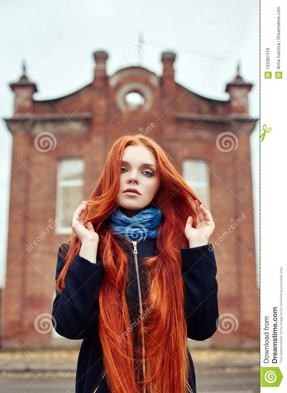 3c080850e4b Woman with long red hair walks in autumn on the street. Mysterious dreamy  look and the image of the girl. Redhead woman walking in the autumn the  city.