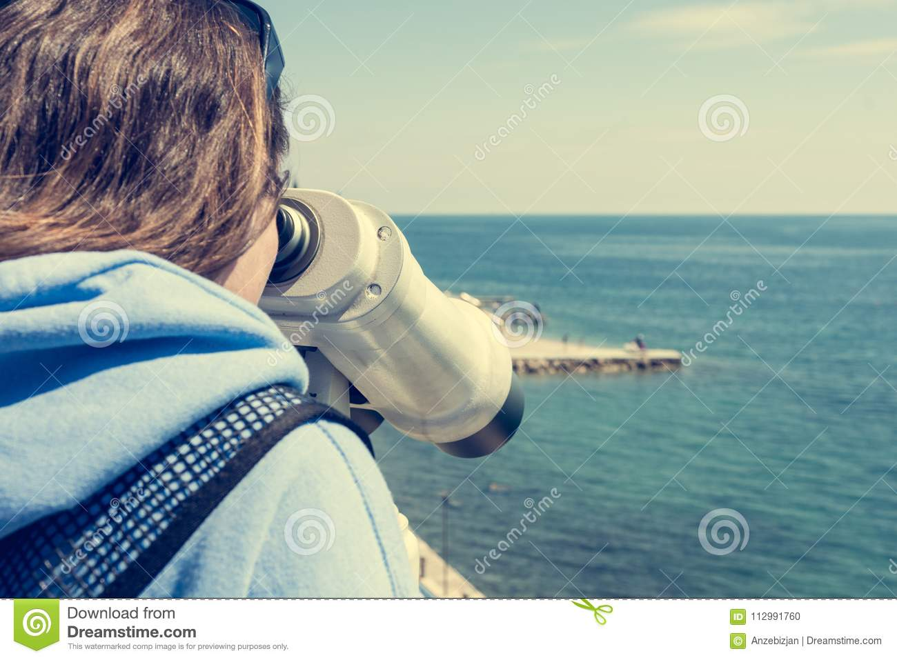 Woman looking through coin operated binoculars at seaside.