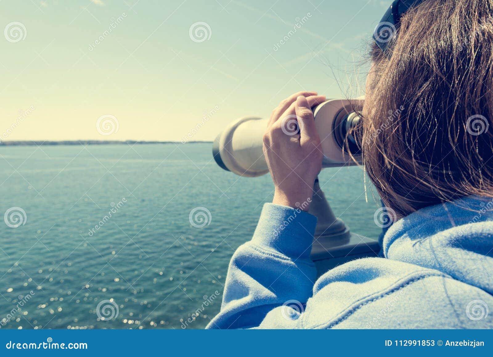 Woman looking through coin operated binoculars at seaside.