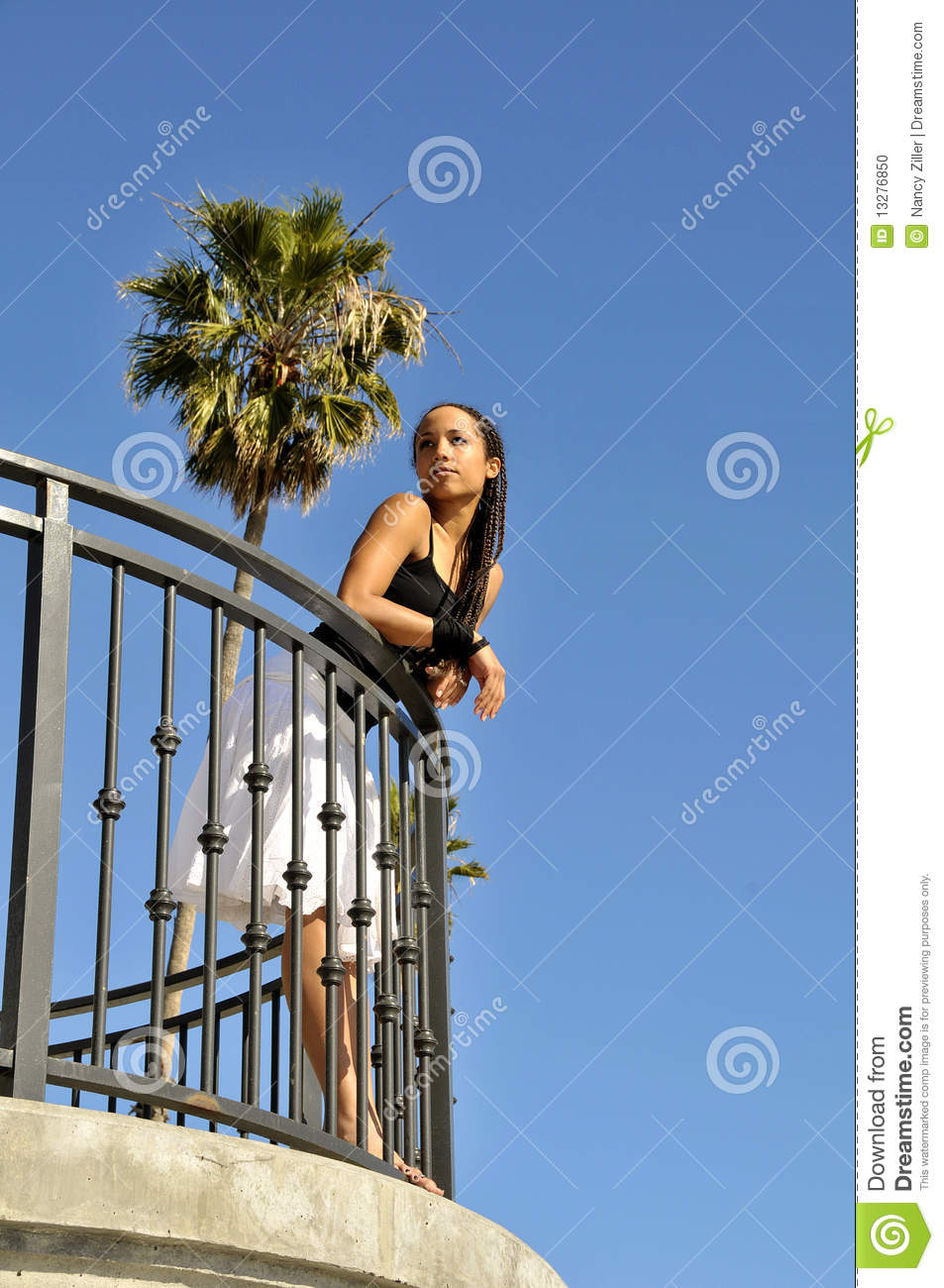 Woman looking gazing off in distance from balcony stock for From the balcony