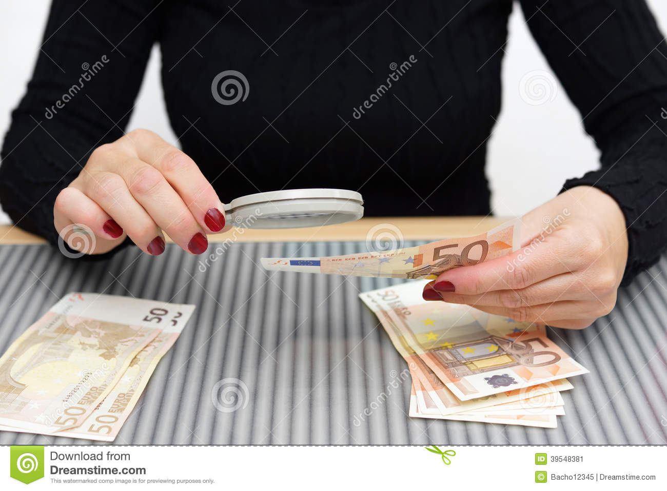 Woman is looking through a magnifying glass for counterfeit