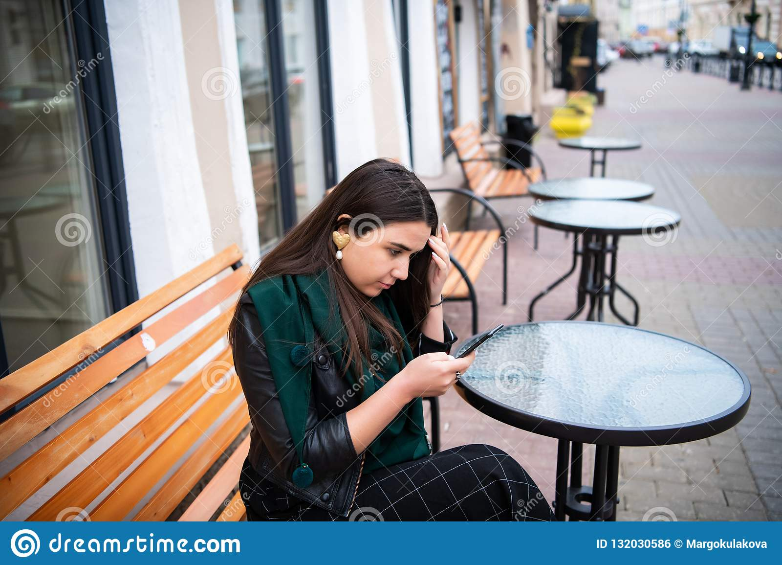 Woman looking at smartphone at street cafe feeling upset.