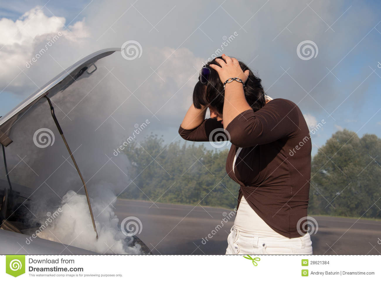 Woman looking at smoking car engine