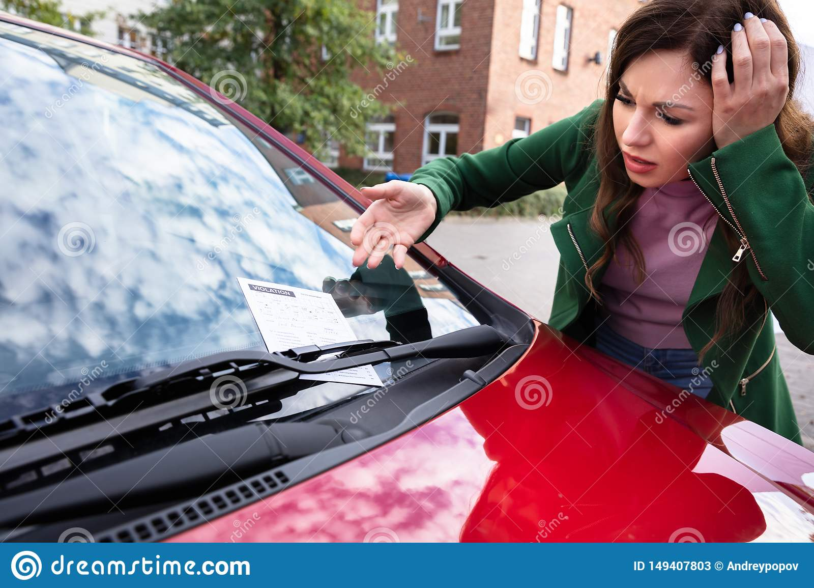 Woman Looking At Ticket Fine For Parking Violation On Car