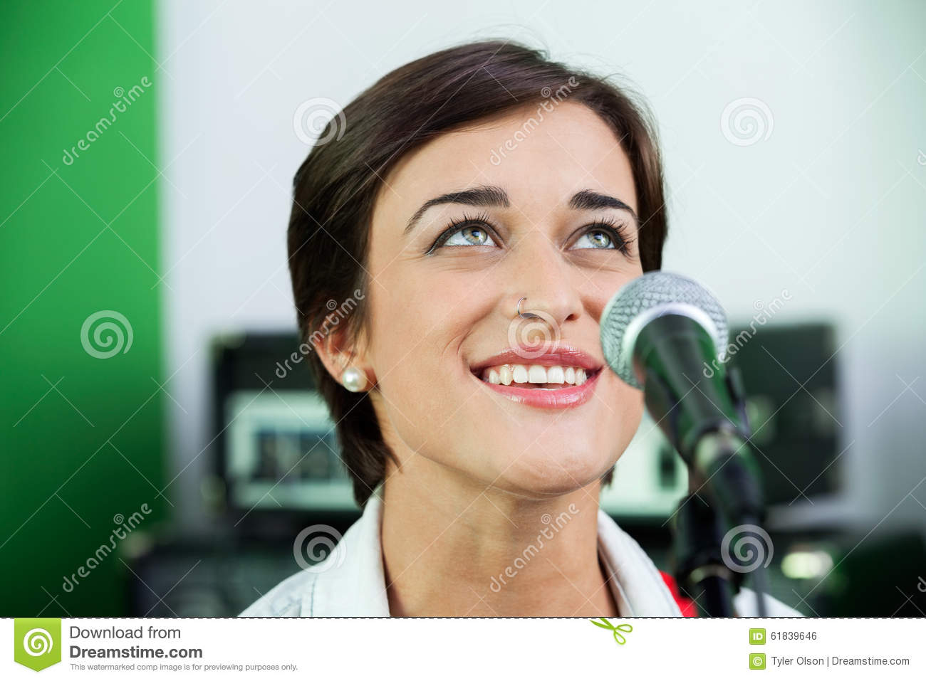 Woman Looking Up While Singing In Recording Studio