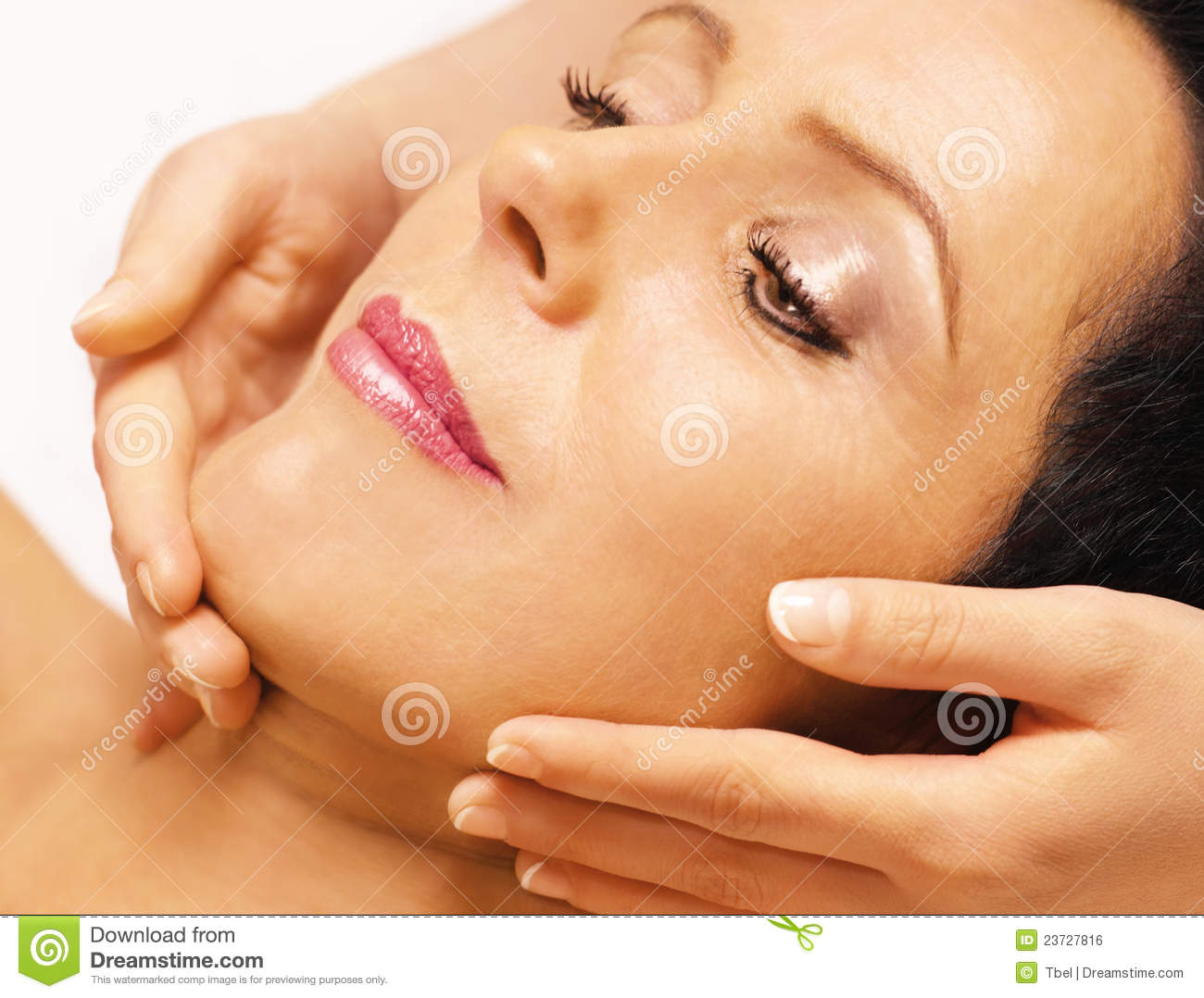 Woman lying, gets massage, reiki, on her face