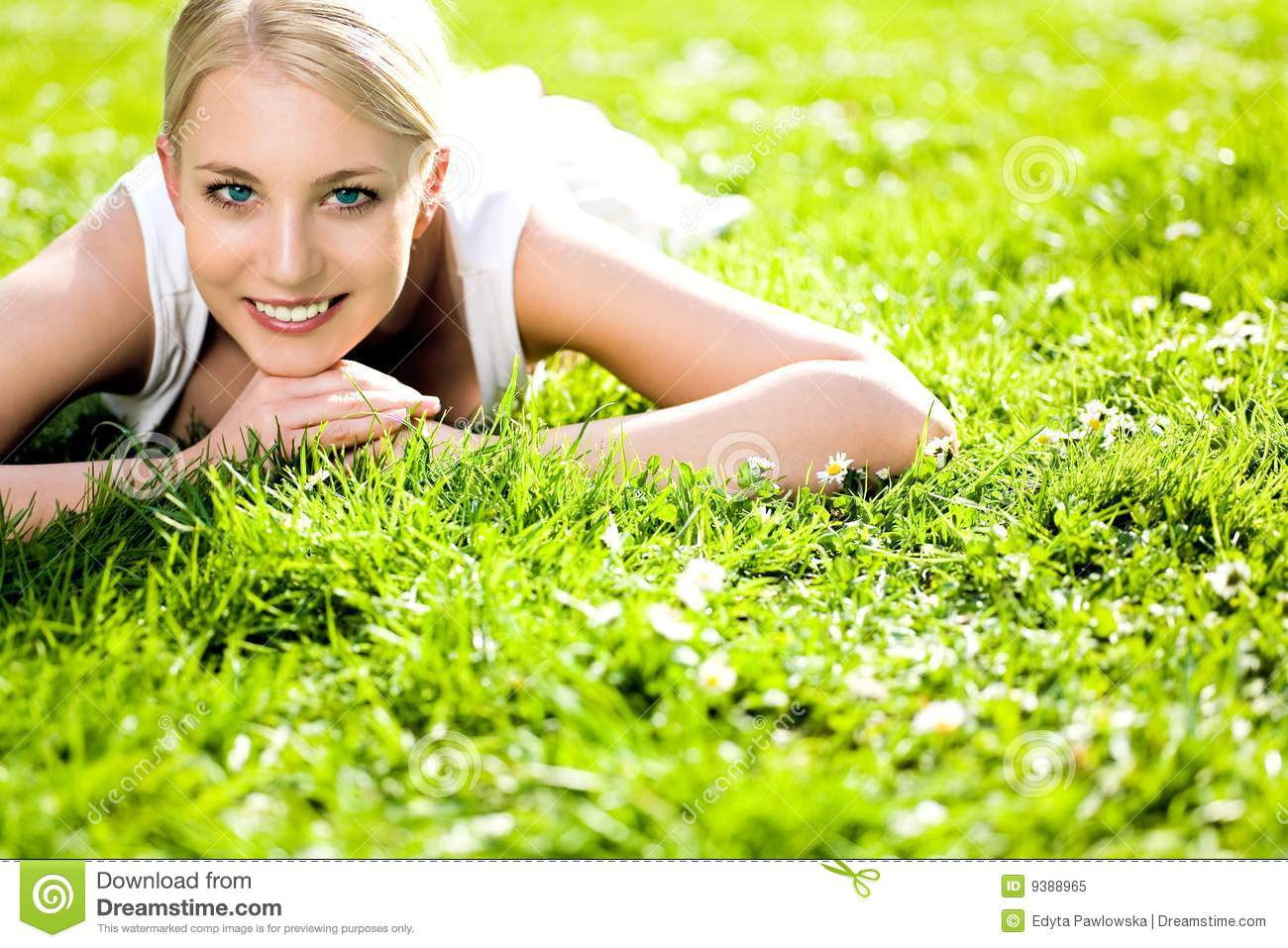 Stock Photo of Young nude woman curled up in tall grass
