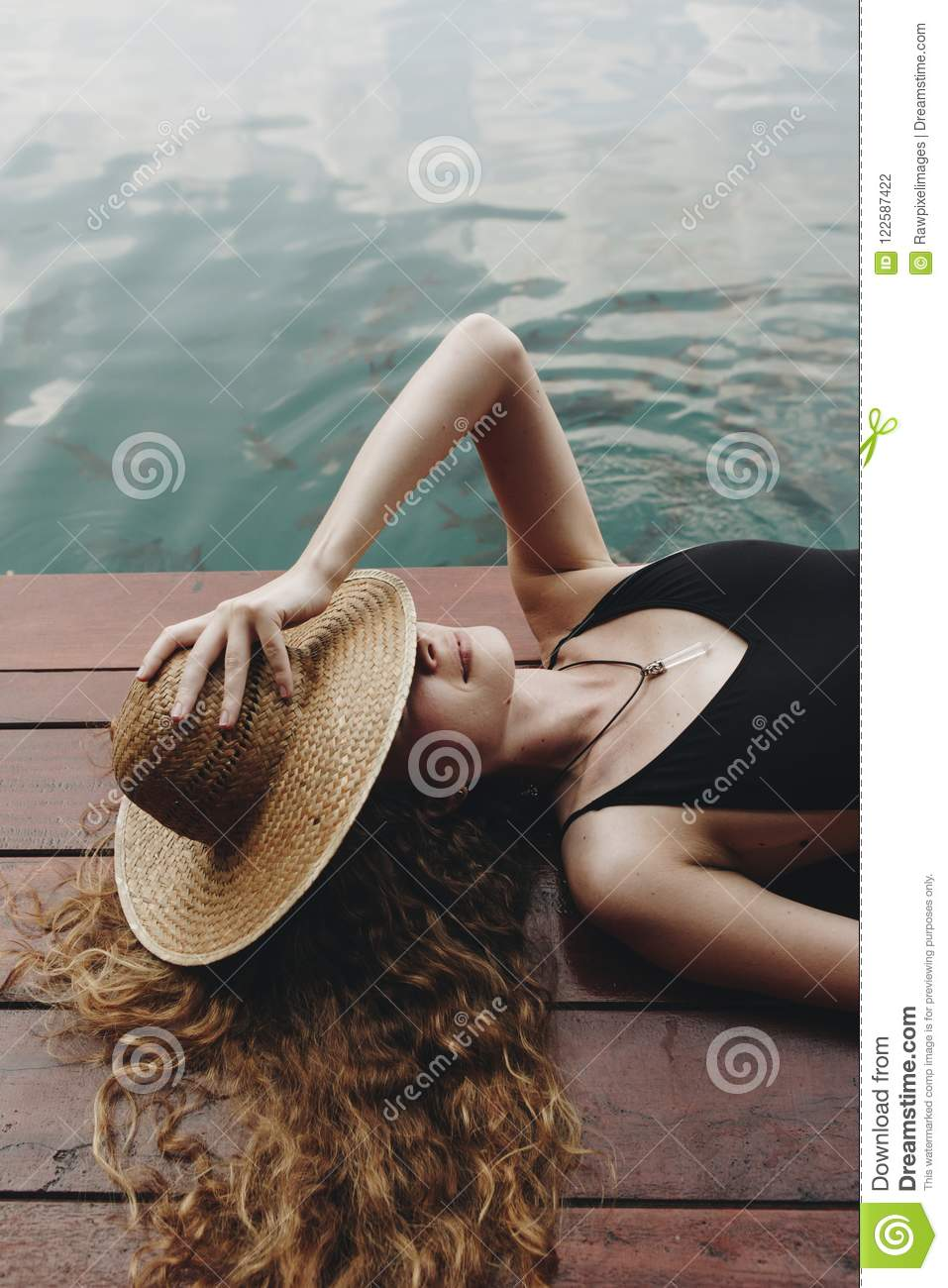 Woman Lying On A Wooden Deck By The Lake Stock Photo ...