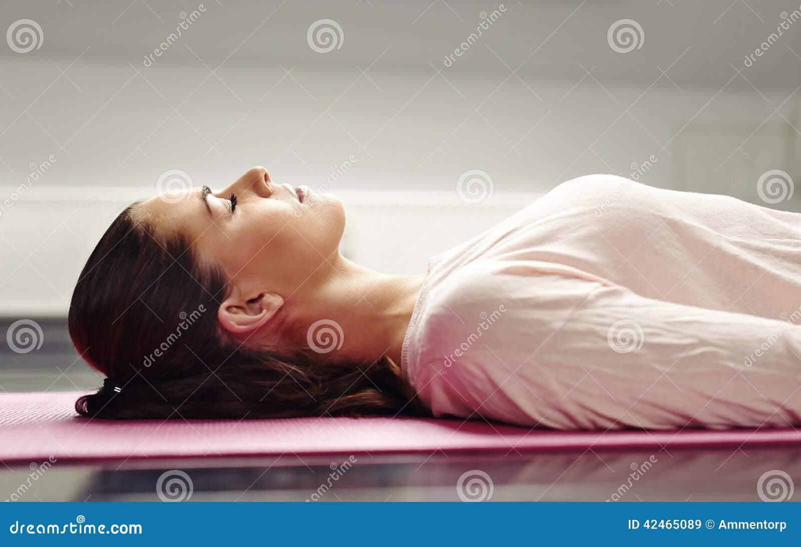 Woman lying on yoga mat relaxing her muscles