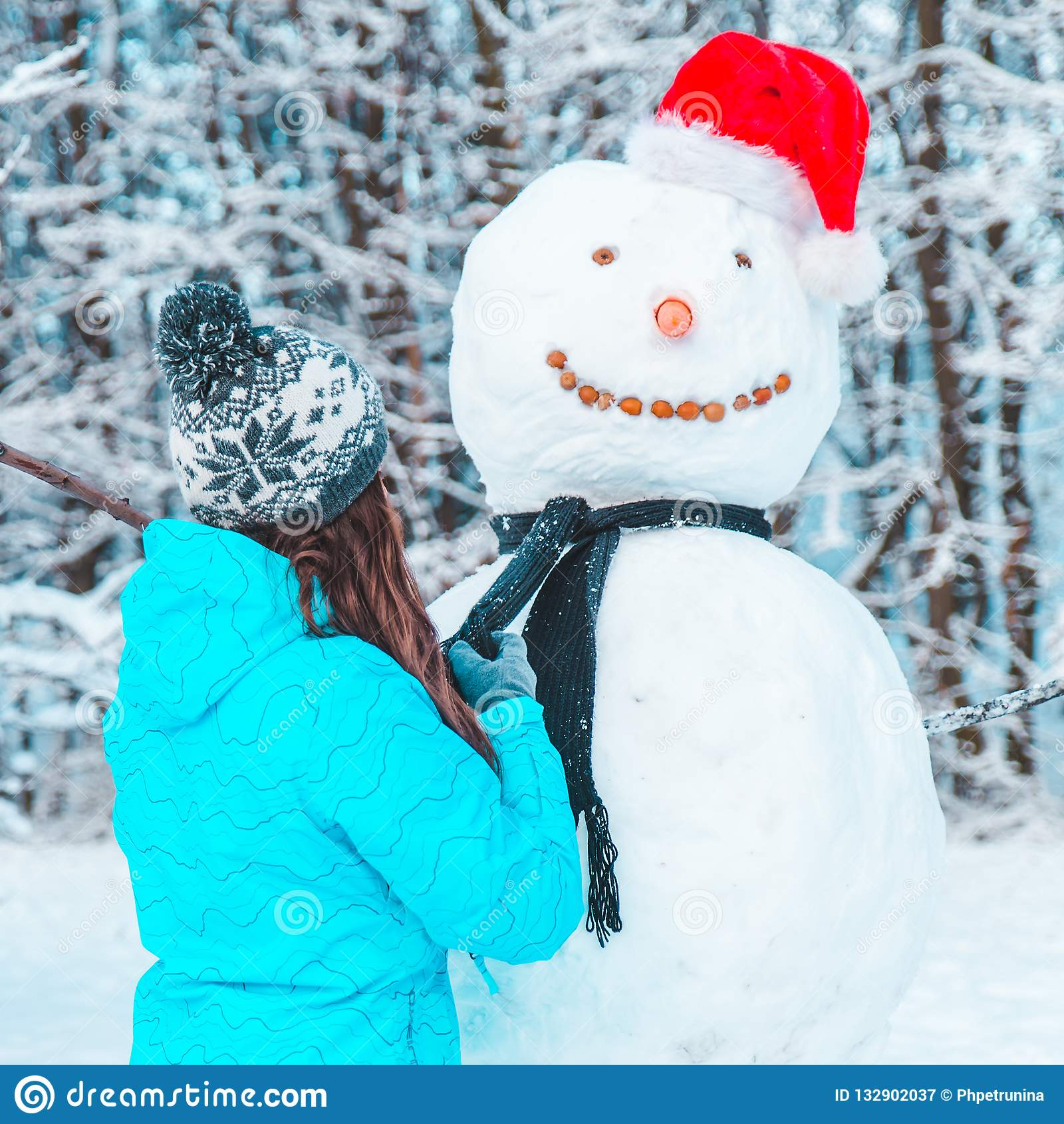 Woman make a snowman in frosty winter day