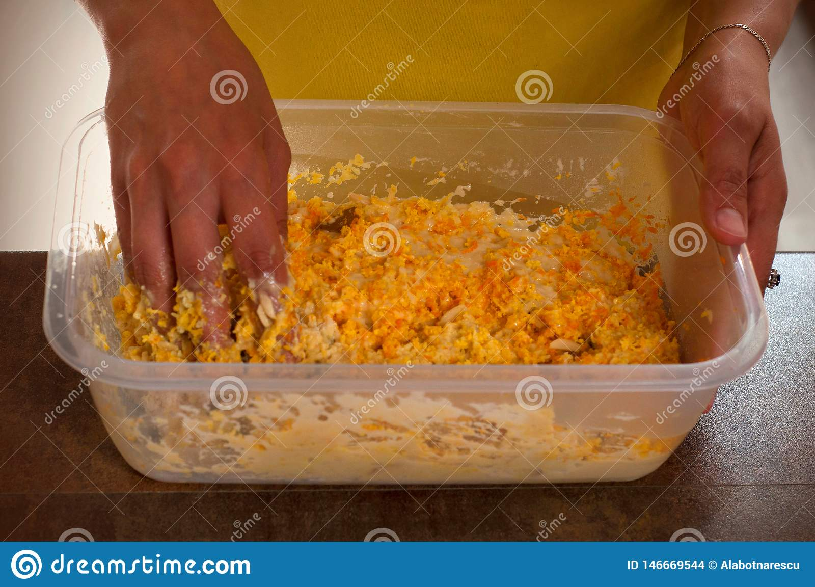 Woman makes dough for Easter cake with dried raisin, chopped almonds and crushed mandarin shells over brown wooden background.