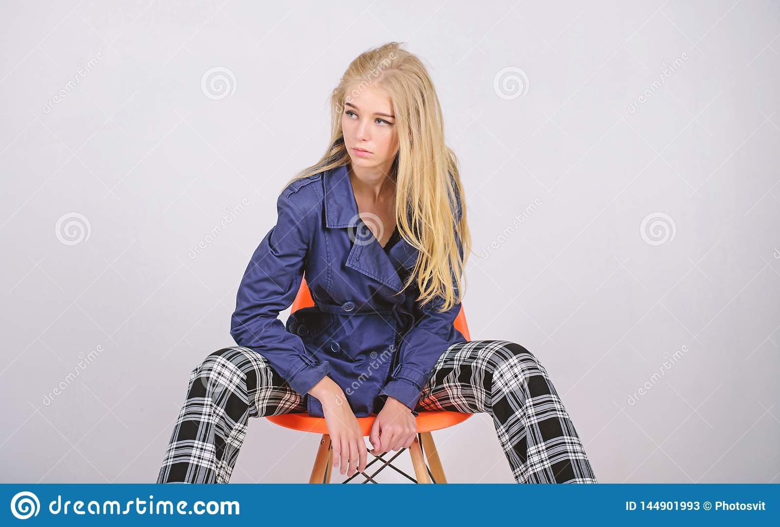 Woman makeup face posing coat at modern chair. Fashionable coat. Clothes and accessory. Mixing styles. Girl fashion