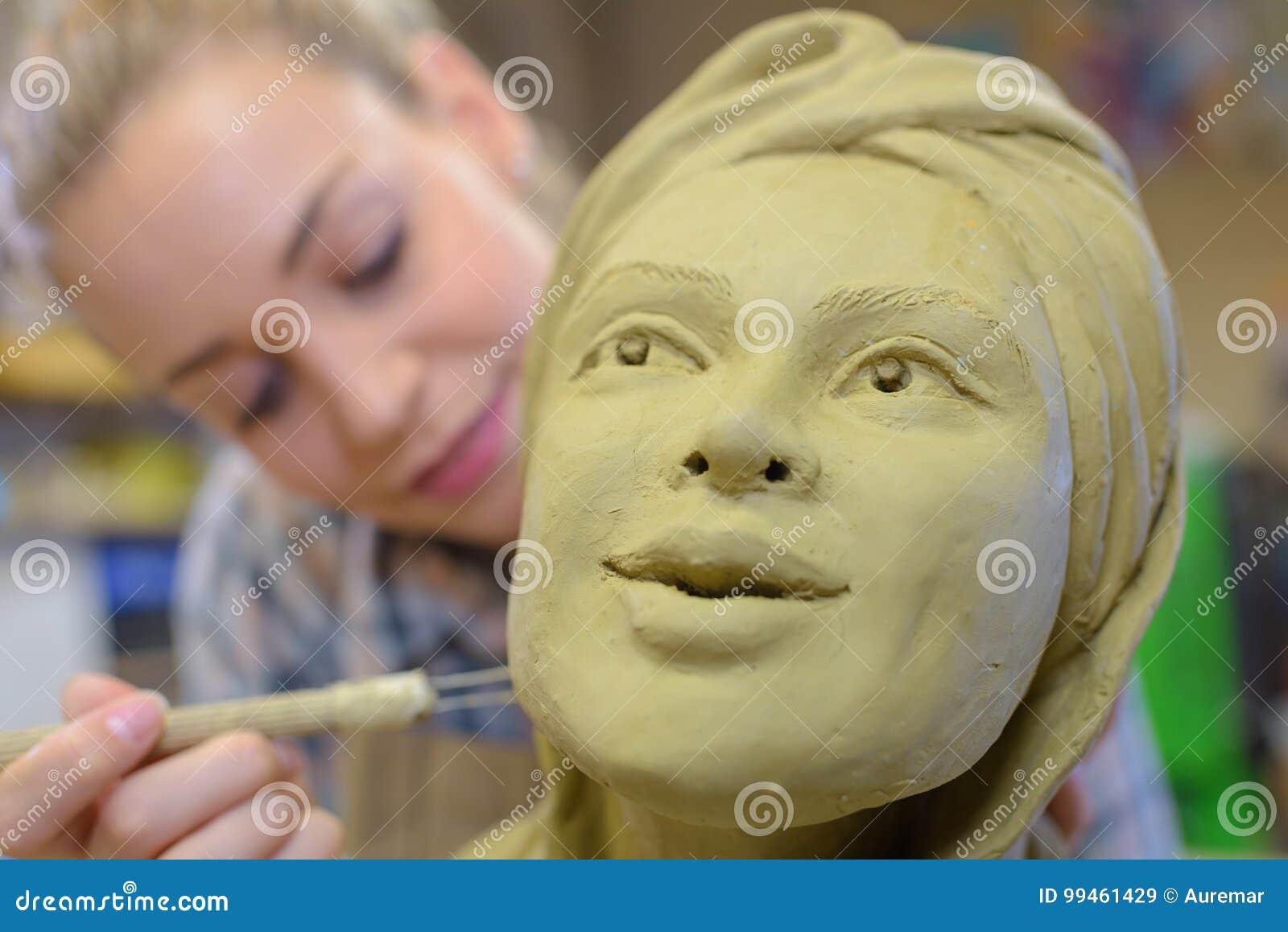 Woman making ceramic face in art class