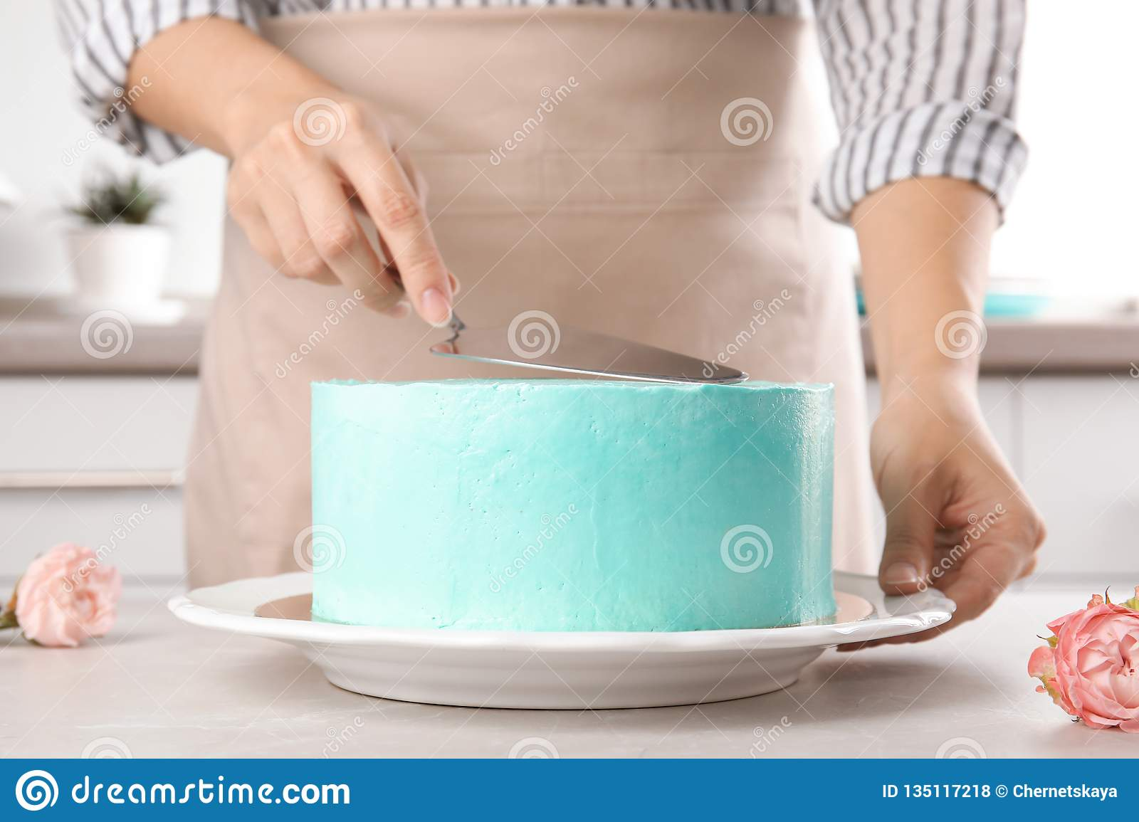 Woman making fresh delicious birthday cake in kitchen
