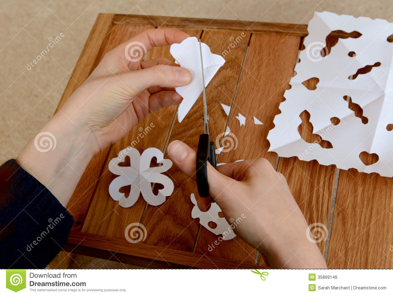Woman making paper snowflakes at a wooden craft table for Craft made by paper
