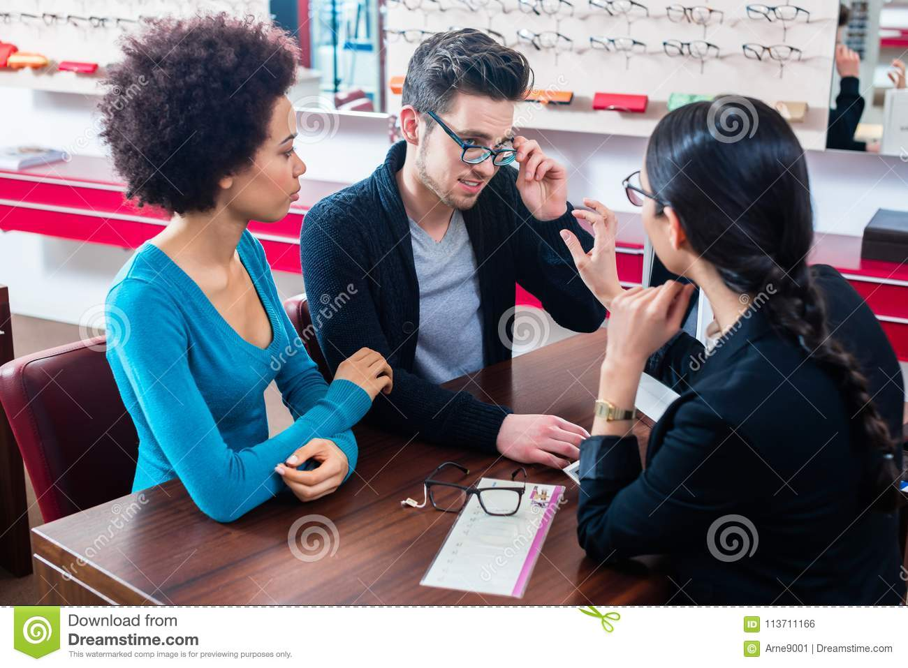 9f95ed7b7c Woman and men buying glasses at optician store getting advice from saleslady